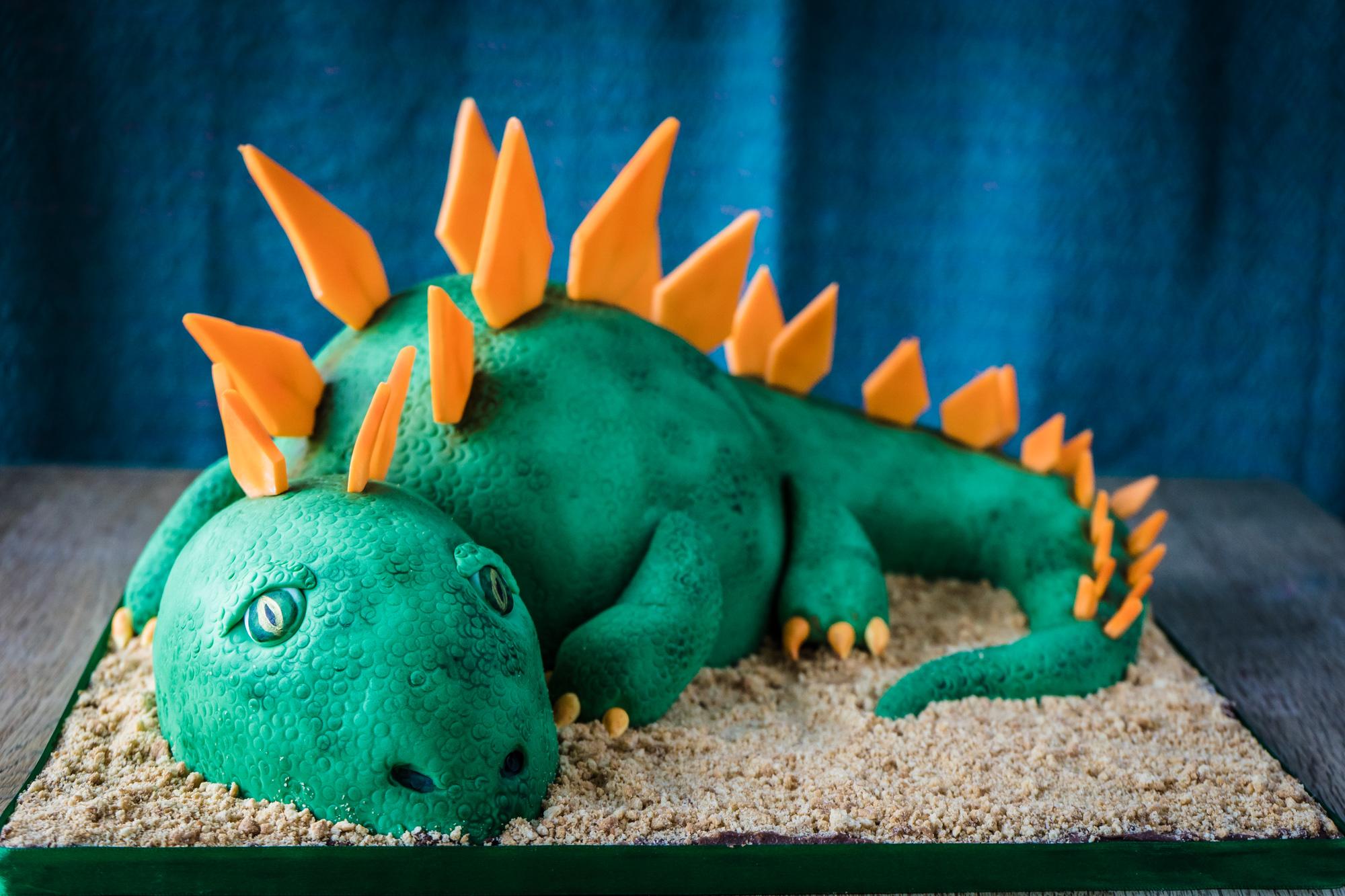 Resting dinosaur on sand birthday cake