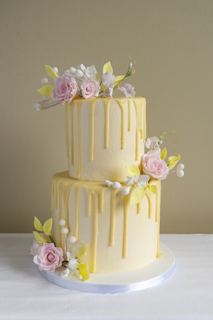 Lemon yellow drip cake with fondant flowers