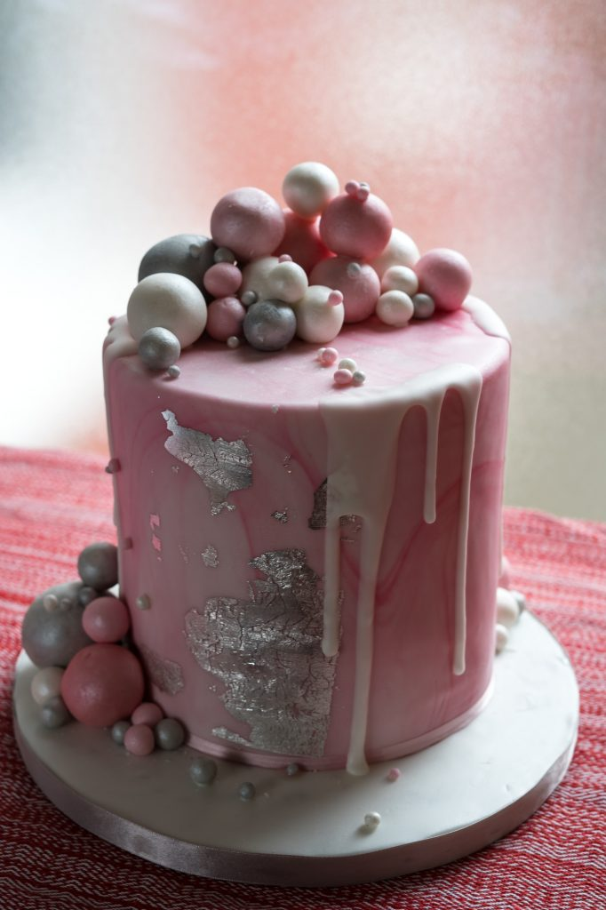 Pink and silver balls drip cake